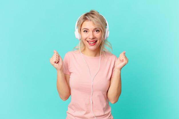 Mulher jovem e bonita se sentindo chocada, rindo e comemorando o sucesso. ouvir conceito de música