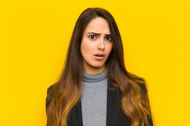 Mulher jovem e bonita se sentindo confusa e confusa, com uma expressão idiota e aturdida, olhando para algo trabalho inesperado ou conceito de negócio