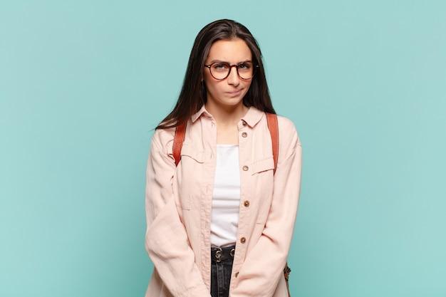 Mulher jovem e bonita se sentindo confusa e em dúvida, pensando ou tentando escolher ou tomar uma decisão. conceito de estudante
