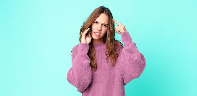 Mulher jovem e bonita se sentindo confusa e intrigada, mostrando que você é maluca e usando um smartphone
