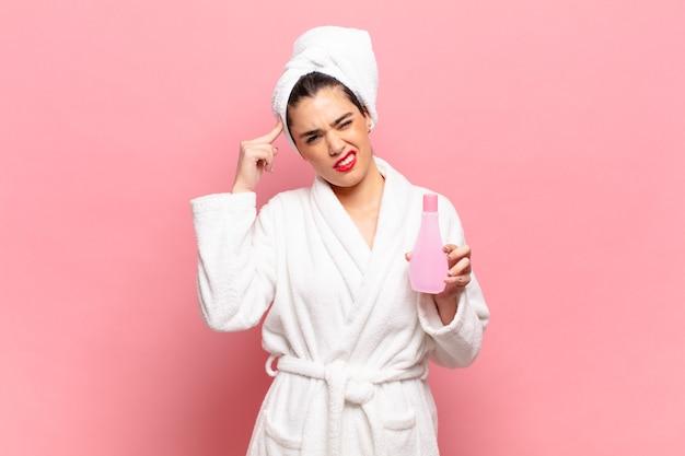 Mulher jovem e bonita se sentindo confusa e perplexa, mostrando que você está louco, louco ou fora de si. conceito de roupão de banho e limpeza facial