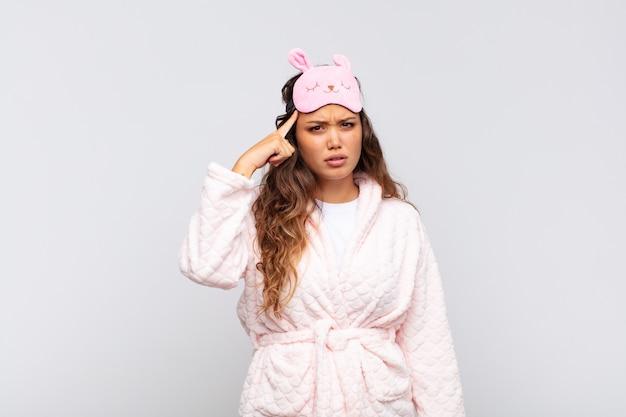 Mulher jovem e bonita se sentindo confusa e perplexa, mostrando que você está louco, louco ou maluco de pijama
