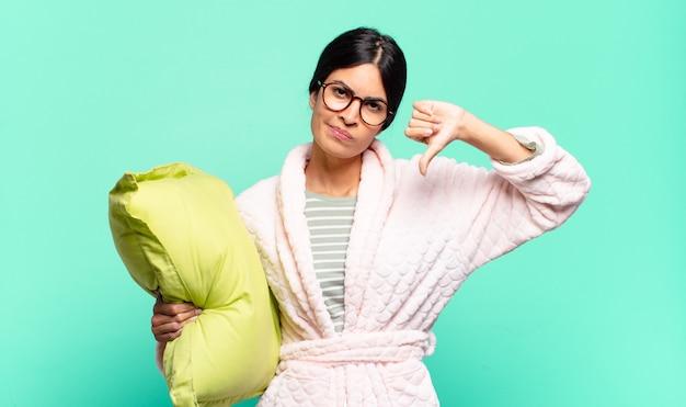 Mulher jovem e bonita se sentindo confusa, sem noção e insegura, avaliando o que há de bom e de ruim em diferentes opções ou escolhas. conceito de pijama