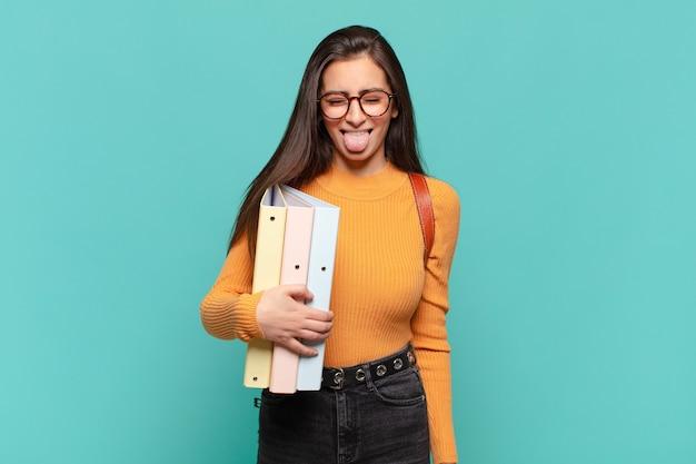 Mulher jovem e bonita se sentindo enojada e irritada, mostrando a língua, não gostando de algo nojento e nojento. conceito de estudante