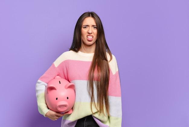 Mulher jovem e bonita se sentindo enojada e irritada, mostrando a língua, não gostando de algo nojento e nojento