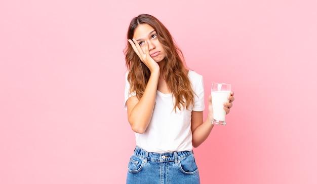 Mulher jovem e bonita se sentindo entediada, frustrada e com sono depois de um dia cansativo e segurando um copo de leite