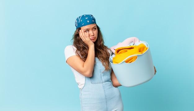 Mulher jovem e bonita se sentindo entediada, frustrada e com sono depois de um dia cansativo segurando uma cesta de roupas para lavar