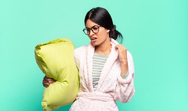 Mulher jovem e bonita se sentindo estressada, ansiosa, cansada e frustrada, puxando o pescoço da camisa, parecendo frustrada com o problema. conceito de pijama