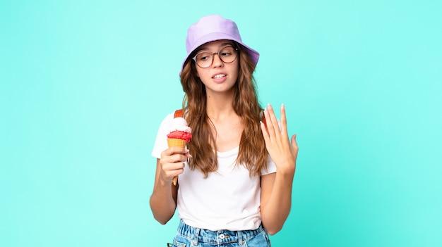 Mulher jovem e bonita se sentindo estressada, ansiosa, cansada e frustrada segurando um sorvete. conceito de verão