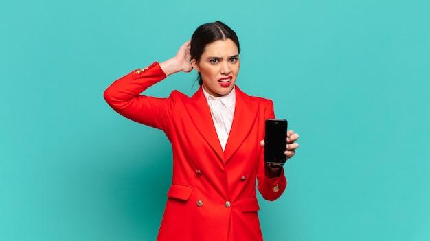Mulher jovem e bonita se sentindo estressada, preocupada, ansiosa ou com medo, com as mãos na cabeça, entrando em pânico por engano. conceito de smartphone