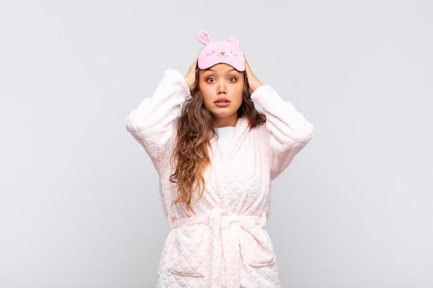 Mulher jovem e bonita se sentindo estressada, preocupada, ansiosa ou com medo, com as mãos na cabeça, entrando em pânico por engano usando pijama