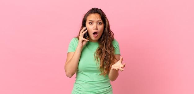 Mulher jovem e bonita se sentindo extremamente chocada e surpresa, segurando um telefone inteligente