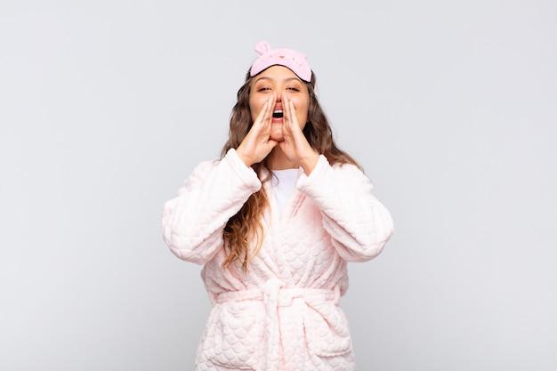 Mulher jovem e bonita se sentindo feliz, animada e positiva, dando um grande grito com as mãos perto da boca, gritando de pijama