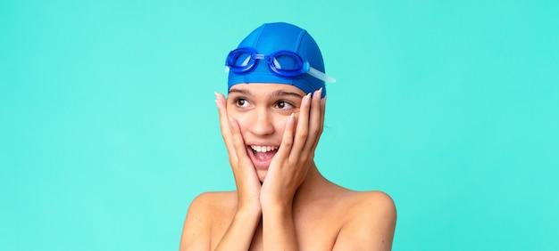 Mulher jovem e bonita se sentindo feliz, animada e surpresa com óculos de natação