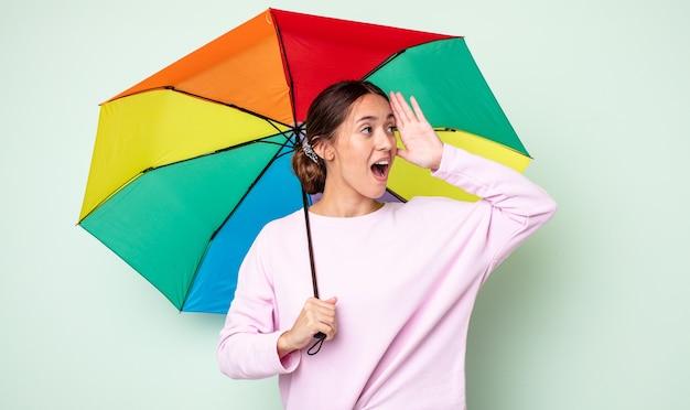 Mulher jovem e bonita se sentindo feliz, animada e surpresa. conceito de guarda-chuva