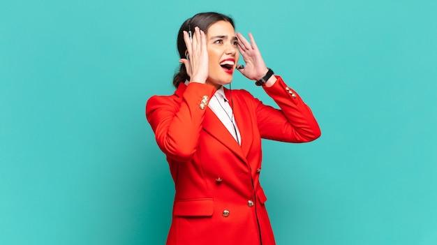 Mulher jovem e bonita se sentindo feliz, animada e surpresa, olhando para o lado com as duas mãos no rosto. conceito de telemarketing