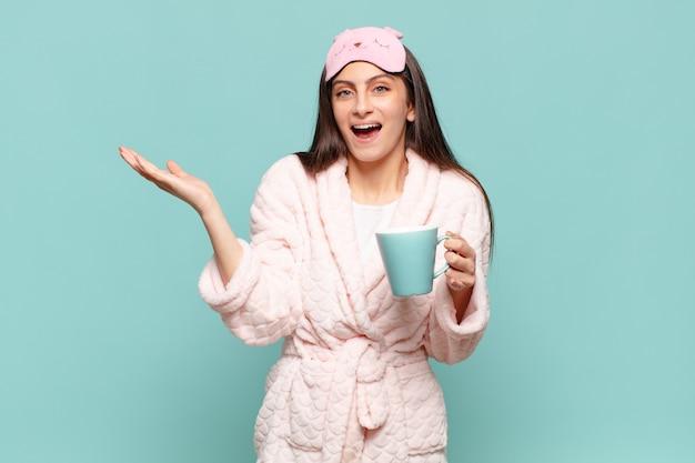Mulher jovem e bonita se sentindo feliz, animada, surpresa ou chocada, sorrindo e atônita com algo inacreditável. acordar de pijama conceito