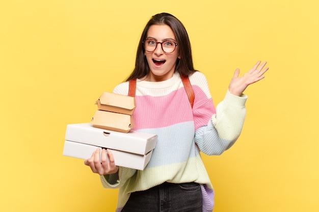 Mulher jovem e bonita se sentindo feliz, animada, surpresa ou chocada, sorrindo e atônita com algo inacreditável. pegue um conceito de fast food fácil