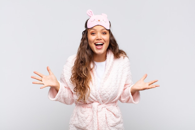 Mulher jovem e bonita se sentindo feliz, animada, surpresa ou chocada, sorrindo e espantada com algo inacreditável de pijama