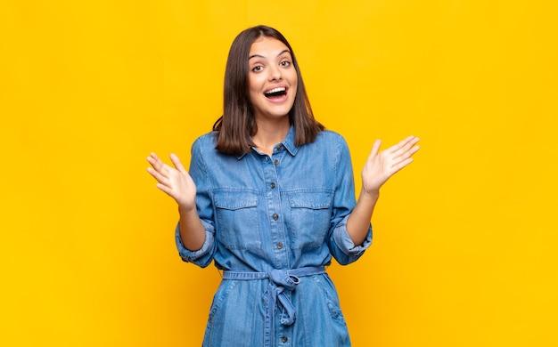 Mulher jovem e bonita se sentindo feliz, animada, surpresa ou chocada, sorrindo e espantada com algo inacreditável