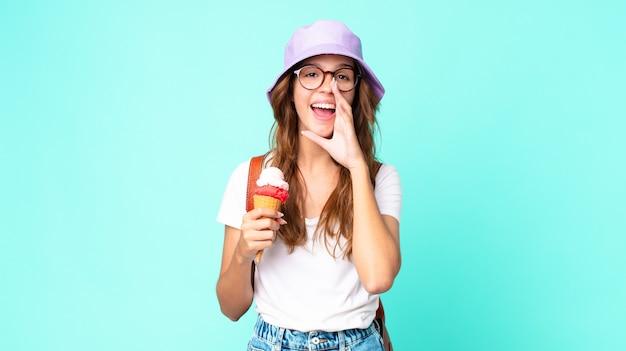 Mulher jovem e bonita se sentindo feliz, dando um grande grito com as mãos perto da boca segurando um sorvete. conceito de verão