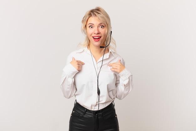 Mulher jovem e bonita se sentindo feliz e apontando para si mesma com um animado. conceito de telemarketing