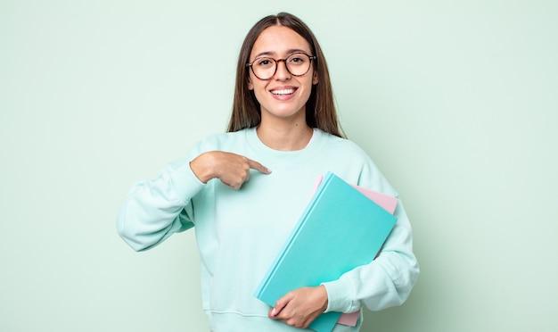 Mulher jovem e bonita se sentindo feliz e apontando para si mesma com um animado. estudante universitário