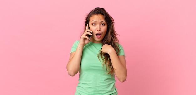 Mulher jovem e bonita se sentindo feliz e apontando para si mesma com um telefone inteligente animado e segurando
