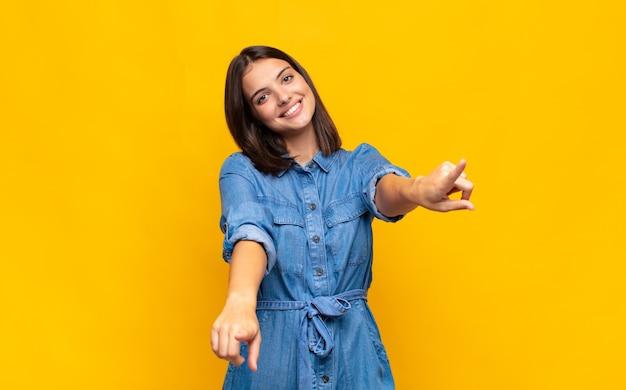Mulher jovem e bonita se sentindo feliz e confiante, apontando para a frente com as duas mãos e rindo, escolhendo você