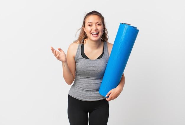 Mulher jovem e bonita se sentindo feliz e surpresa ao perceber uma solução ou ideia e segurando um tapete de ioga