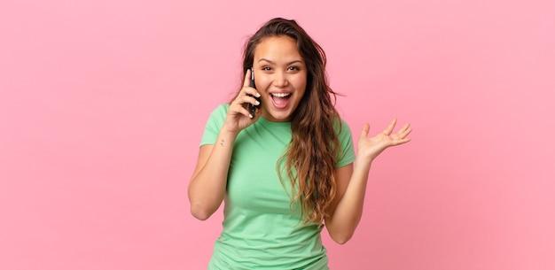 Mulher jovem e bonita se sentindo feliz e surpresa com algo inacreditável e segurando um smartphone