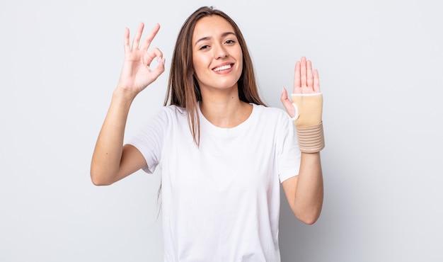 Mulher jovem e bonita se sentindo feliz, mostrando aprovação com um gesto certo. conceito de bandagem de mão