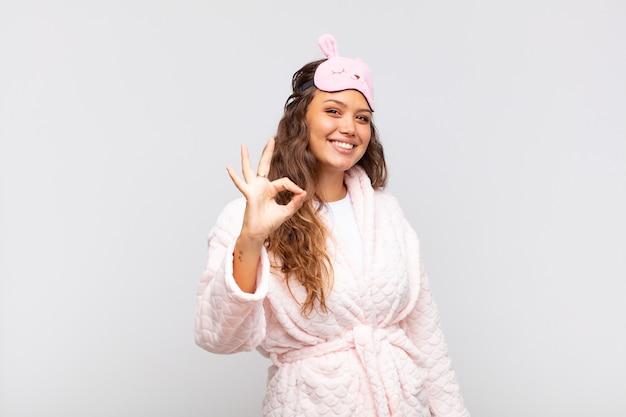 Mulher jovem e bonita se sentindo feliz, relaxada e satisfeita, mostrando aprovação com gesto de ok, sorrindo de pijama