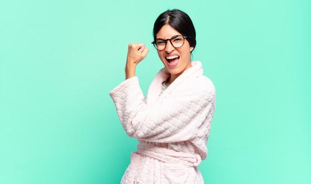 Mulher jovem e bonita se sentindo feliz, satisfeita e poderosa, flexionando o ajuste e bíceps musculosos, parecendo forte depois da academia. conceito de pijama
