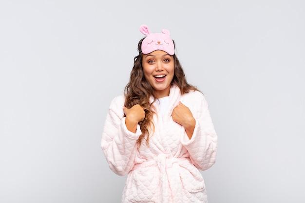 Mulher jovem e bonita se sentindo feliz, surpresa e orgulhosa, apontando para si mesma com um olhar animado e surpreso de pijama