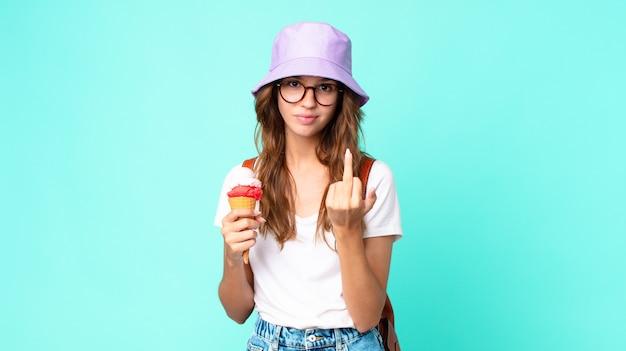 Mulher jovem e bonita se sentindo irritada, irritada, rebelde e agressiva segurando um sorvete. conceito de verão