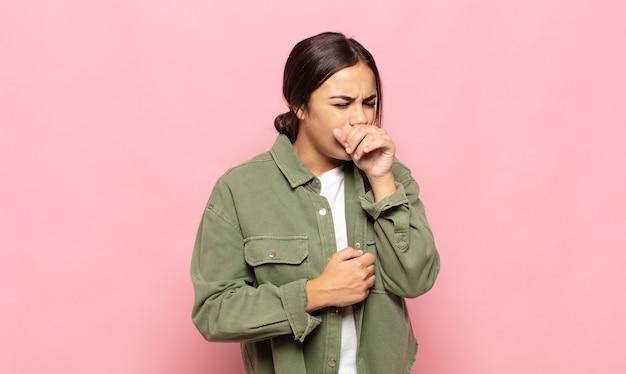 Mulher jovem e bonita se sentindo mal com dor de garganta e sintomas de gripe, tosse com a boca coberta