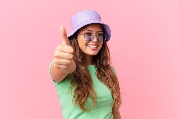 Mulher jovem e bonita se sentindo orgulhosa, sorrindo positivamente com o polegar para cima. conceito de verão