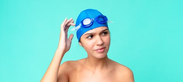 Mulher jovem e bonita se sentindo perplexa e confusa, coçando a cabeça com óculos de natação
