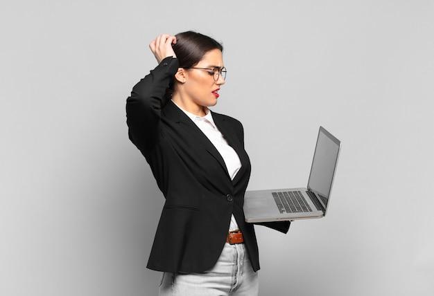 Mulher jovem e bonita se sentindo perplexa e confusa, coçando a cabeça e olhando para o lado. conceito de laptop