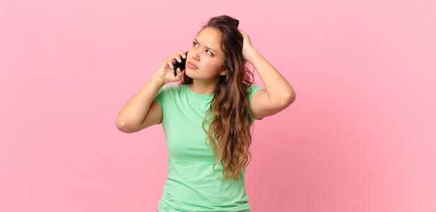 Mulher jovem e bonita se sentindo perplexa e confusa, coçando a cabeça e segurando um telefone inteligente
