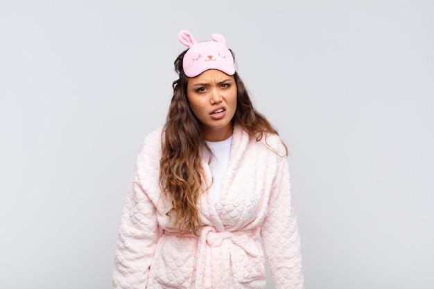 Mulher jovem e bonita se sentindo perplexa e confusa, com uma expressão muda e atordoada olhando para algo inesperado de pijama