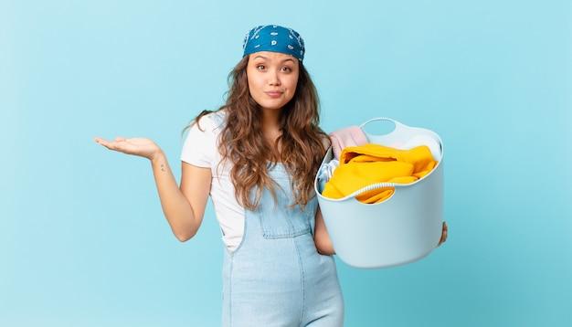 Mulher jovem e bonita se sentindo perplexa e confusa, duvidando e segurando uma cesta de lavar roupas