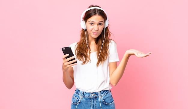 Mulher jovem e bonita se sentindo perplexa e confusa e duvidando com fones de ouvido e um smartphone