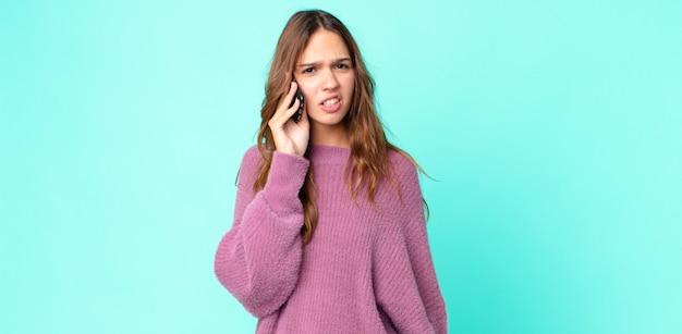 Mulher jovem e bonita se sentindo perplexa e confusa e usando um smartphone