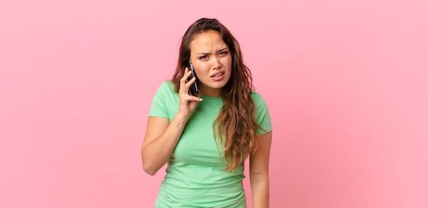 Mulher jovem e bonita se sentindo perplexa e confusa, segurando um telefone inteligente