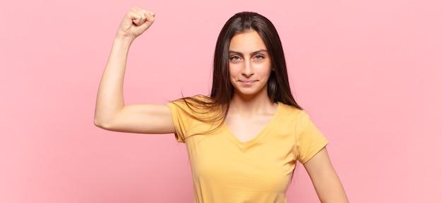 Mulher jovem e bonita se sentindo séria, forte e rebelde, levantando o punho, protestando ou lutando pela revolução