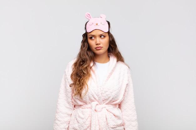 Mulher jovem e bonita se sentindo triste, chateada ou com raiva e olhando para o lado com uma atitude negativa, franzindo a testa em desacordo e vestindo pijama