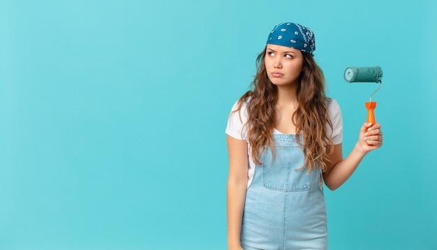 Mulher jovem e bonita se sentindo triste, chateada ou com raiva, olhando para o lado e pintando uma parede