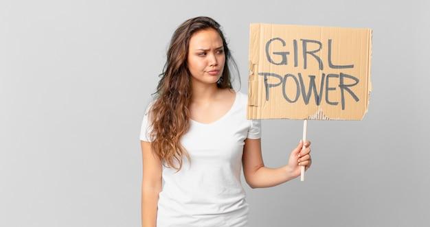 Mulher jovem e bonita se sentindo triste, chateada ou com raiva, olhando para o lado e segurando uma bandeira do poder feminino